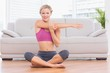 Smiling blonde sitting in lotus pose stretching arms