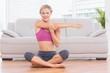 Smiling blonde sitting in lotus pose stretching arms