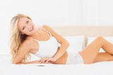 Young blonde lying on bed smiling at camera