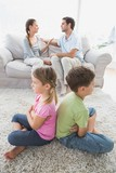 Siblings sitting back to back while parents are arguing