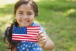 Young girl holding the American flag at park - 62444954