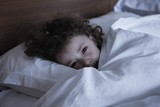 Close-up portrait of a girl resting in bed