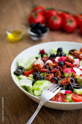 Fresh vegetable salad on a plate with vintage wooden background