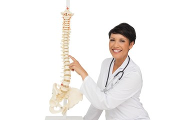 Smiling female doctor pointing at skeleton model