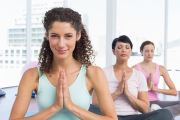 Women with joined hands at fitness studio