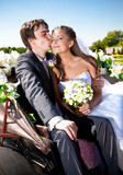 groom kissing bride in cheek on bench at park