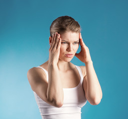 Young woman touching her head in pain frowning.