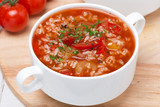 tomato soup with rice, vegetables and herbs, top view