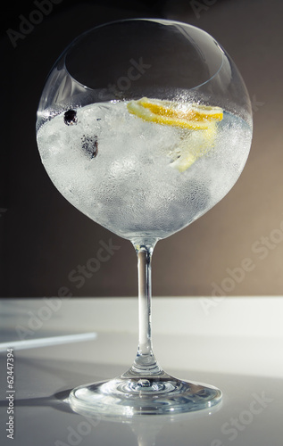 Gin tonic cocktail over a club bar background
