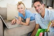 Portrait of smiling couple doing online shopping at home