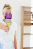 Blurred woman holding out paint brush at new house