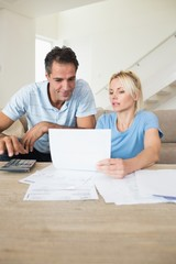 Concentrated couple with bills and calculator in living room