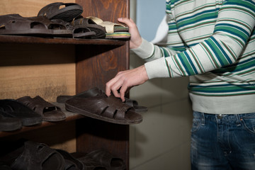 Young Man Takes Slippers To Use Them