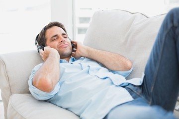 Happy handsome man lying on sofa listening to music