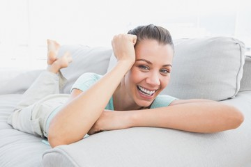 Cheerful woman lying on couch smiling at camera