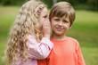 Girl whispering secret into boy's ear at park