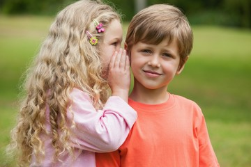 Girl whispering secret into boy's ear at park