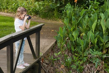 Side view of a girl looking through binoculars at park