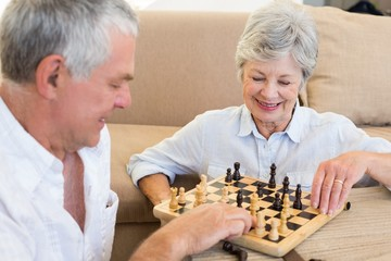 Senior couple sitting on floor playing chess