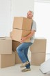 Smiling man carrying cardboard moving boxes