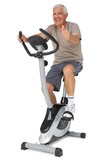 Senior man gesturing thumbs up on stationary bike