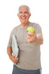 Cheerful senior man with an apple and scales