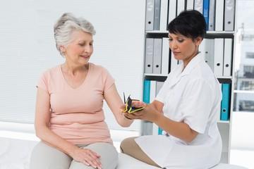 Doctor fixing wrist brace on senior patients hand