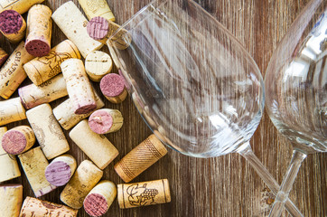 Detail of wine glasses and corks on wooden table