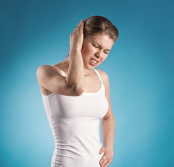 Young female suffering from ear pain over blue background