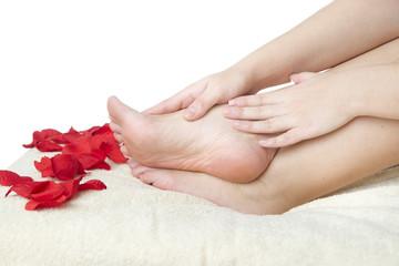 Beautiful female feet and rose petals.