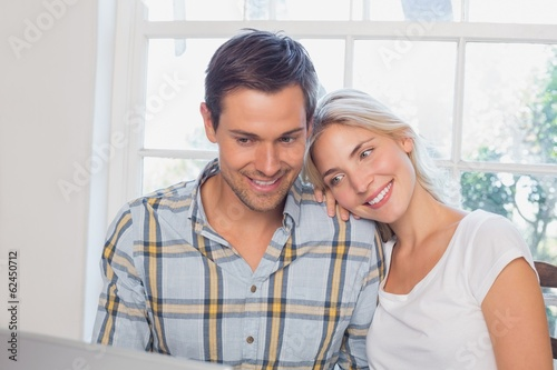 Happy loving couple with laptop at home