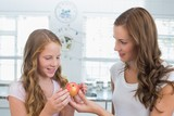 Mother giving apple to her daughter in kitchen