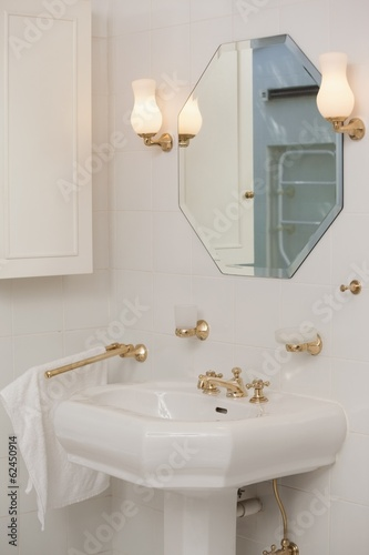 Mirror with lit lamps over sink in bathroom