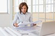 Concentrated businesswoman reading blueprint in office