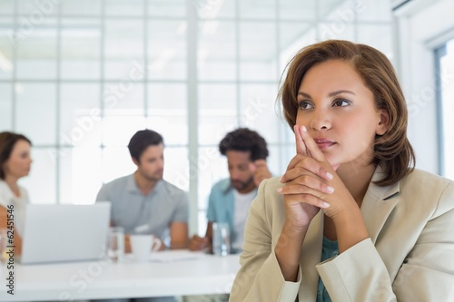 Close-up of serious businesswoman with colleagues in meeting