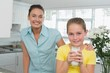 Girl having milk while mother standing by in kitchen