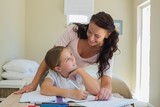 Mother looking at daughter doing homework at table
