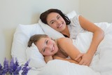 Beautiful mother and daughter lying in bed