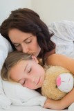 Mother kissing sleeping daughter in bed