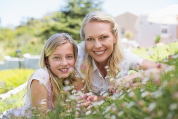 Happy mother and daughter lying in park