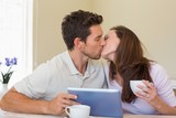 Couple kissing while using digital tablet