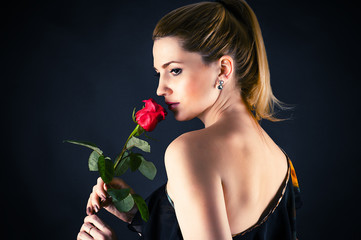 portrait of beautiful woman smelling a rose