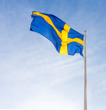 Flag of Sweden waving against blue sky