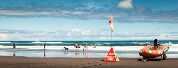 People having fun on Karekare Beach, New Zealand, Panorama