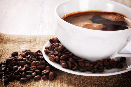 Coffee cup and saucer with coffee beans on a burlap