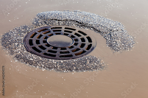 Melted water flows down through the manhole cover on spring day
