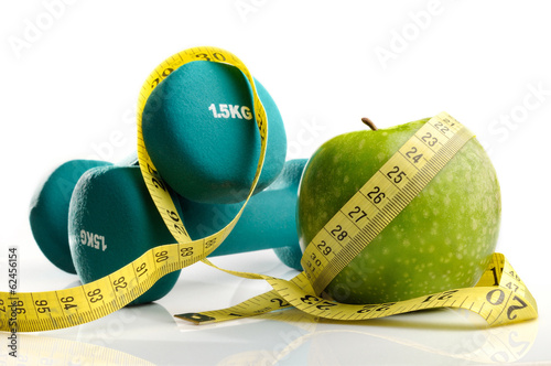 Leinwanddruck Bild healthy apple, measuring tape and dumbbells isolated