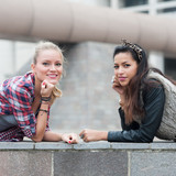 Two girls portrait outdoors with modern building as background.