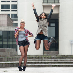 Young women portrait outdoors while jumping with modern building