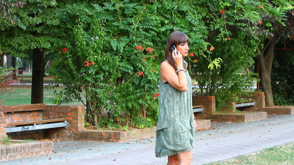 Beautiful Young Woman with Mobile Phone at Park